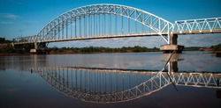 iron bridge for crossing the Carang river, in bright daylight and few clouds. Tanjungpinang, Riau Islands, Indonesia