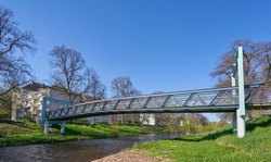 Iron bridge over a small river for pedestrians against the blue sky in a European city, in spring. Clean City Concept, text space