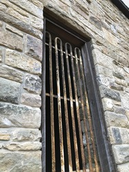 Iron caged window on stone walled building