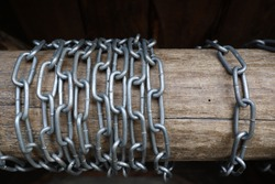 iron chain rings are wrapped around a wooden log