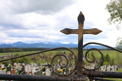 Iron cross on the gate to the cemetery. In the background the Tatra Mountains.