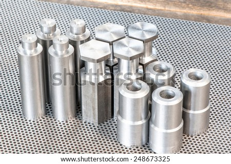 Iron details - shafts bolts nuts and cylinders. Metal engineering. Lathe milling and drilling technology. CNC industry.