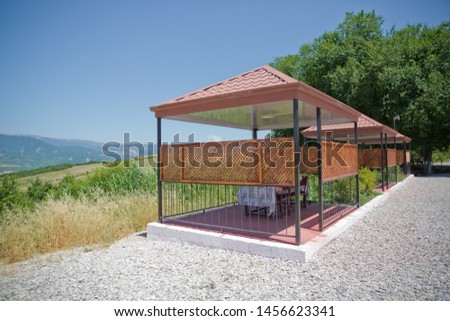 Iron gazebo mounted on concrete foundation with roof still under construction and aluminium ladders next to it situated next to paved road on top of small hill overlooking small mountains. #1456623341