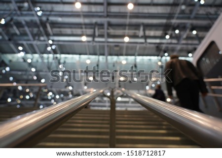 Iron handles of stairs with blurred light on the ceiling and visitors climbing up the stairs to the swiss Autosalon Genf 2019 in Geneva, Switzerland