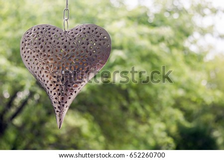 iron heart hanging on a chain on a background of green trees and swinging #652260700