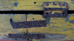 Iron hinges and rusty nails stuck to the boards