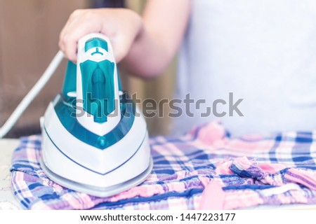 iron in the hand of the girl on the Ironing Board irons and steams clothes
