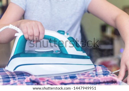 iron in the hand of the girl on the Ironing Board irons and steams clothes #1447949951