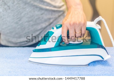 iron in the hand of the girl on the Ironing Board irons and steams clothes #1449417788