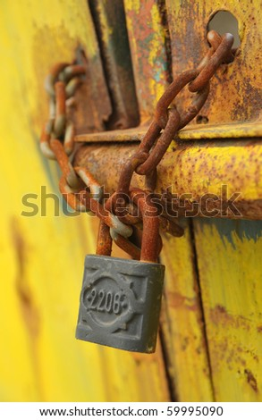 Iron lock and chain on an old rusty door
