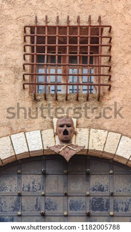 Iron Mask above an old gate in Le Suquet on the Tour du Masque, a tower that is haunted by the ghost of the man in the Iron Mask near the castle of Castre in Cannes, France