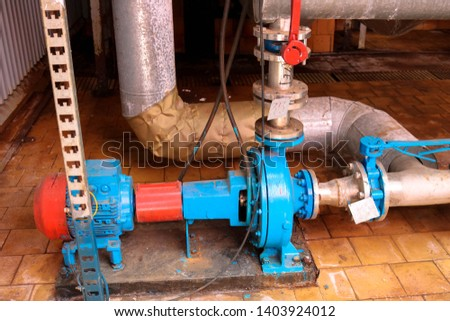 Iron metal centrifugal pumps equipment and pipes with flanges and valves for pumping liquid fuel products at the industrial refinery chemical petrochemical plant shop.
