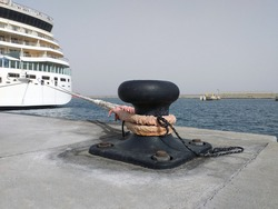 Iron mooring bollard in port with rope and moored cruise ship. Bow of Cruise Ship Tied to Black Bollard with thick rope. Cruise ship at anchor in a port. View of pier background.