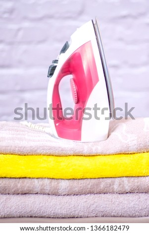 iron on a stack of ironed towels #1366182479