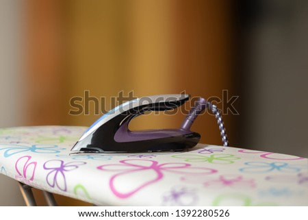 Iron on an ironing board #1392280526
