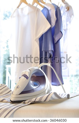 Iron on ironing board with clothes hanging in background
