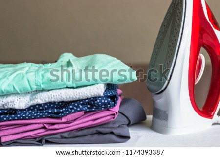Iron on the ironing board and non-ironed clothes #1174393387