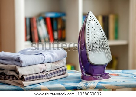 Iron on the ironing board next to a stack of ironed shirts
