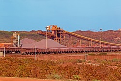 Iron ore stockpile and transfer conveyor with fully loaded rail wagons in Western Cape, South Africa