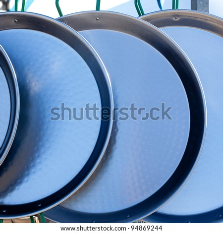 iron paella typical pan from mediterranean Spain in a row - stock photo