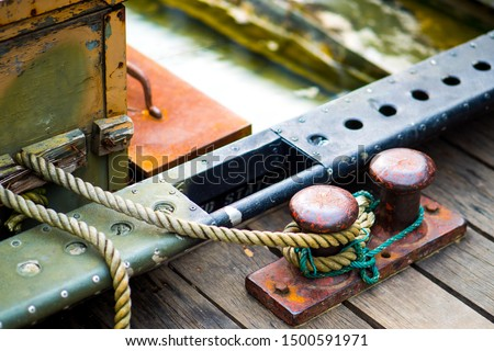 Iron pole tied with ropes for mooring of ships in the port. rope around the poles for ship tong park at the ports.  Boat port near small lake.