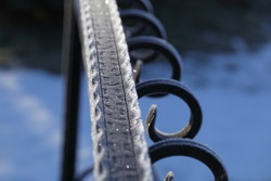 Iron railing covered with morning frost. Snow and ice texture.