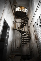 iron spiral staircase in an abandoned factory building, color effect