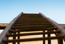 Iron stairs leading to the blue, clear sky. Metal stairway to the sky, background. Rusted and bent staircase which leading to the roof of the antique house. The way to the attic of the old building.