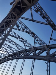 Iron structure of the arched bridge against the blue sky. Metal beams, spans, bolts and rivets