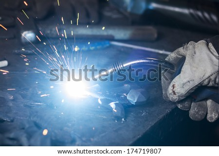 Iron welding with bright light and smoke at manufacturing