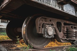 Iron wheels of a train. Metal wheelset from a locomotive. Chassis of the train. The lower part of the wagon. Chassis on rails. The sound of wheels. Abandoned diesel locomotive. Rusty metal