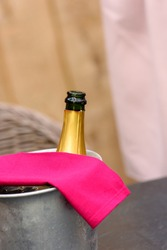 Iron winecooler without cork with a magenta serviette waiting for the guests to arrive against lightbrown wooden background