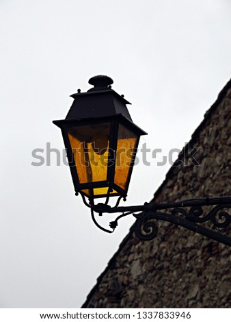 Iron wrought decorative black street lantern with yellow glass. Street light, light pole, lamppost, street lamp, light standard, lamp standard against old stone building and sky background in France