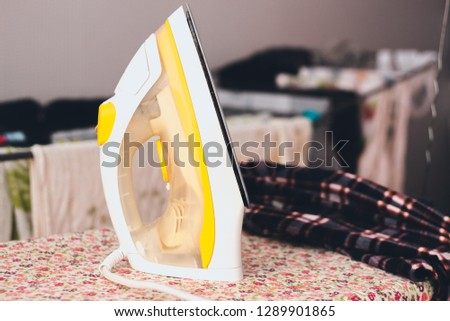 Iron yellow shade stand on the ironing board with patterns of small flowers. Nearby is a shirt with a checkered pattern that needs to be ironed. #1289901865