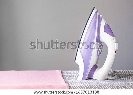Ironed clothes and iron on the ironing board in the room.  Colorful cotton clothes and iron