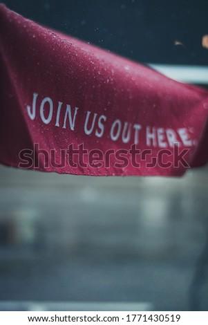 Ironic phrase on an umbrella during a rainstorm