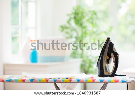 Ironing board and iron with folded clothes. White sunny laundry room with big window. Home chores. Household appliance and device Photo stock ©