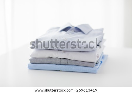 ironing, laundry, clothes, housekeeping and objects concept - close up of ironed and folded shirts on table at home