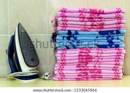 Ironing linen with steam generator. A stack of ironed towels lying next to the iron. Teflon sole plate covered with small holes. #1233065866