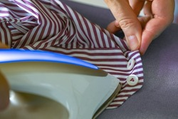 Ironing the sleeve of a shirt with a steam iron. Woman ironing shirt on ironing board with steaming iron