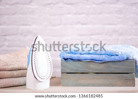 ironing towels and an iron and a laundry box are on the ironing board #1366182485