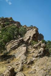 Irregular rock cliff texture and background, stone crags mountain cliff texture and beautiful blue sky in summer season. Kanishok, Sulaymaniyah, Kurdistan, Iraq.
