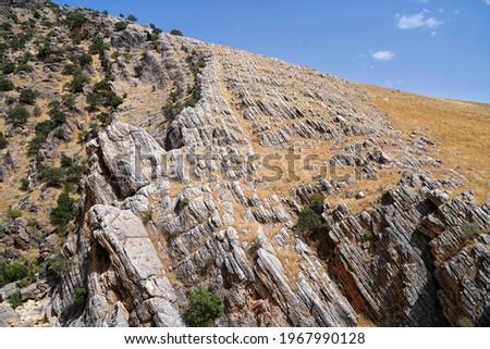 Irregular rock cliff texture and background, stone crags mountain cliff texture and beautiful blue sky in summer season. Kanishok, Sulaymaniyah, Kurdistan, Iraq. Photo stock ©