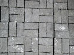 Irregular shaped tiles. Broken concrete path.