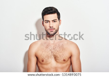 Irresistible man. Handsome man standing shirtless over white background and looking at camera