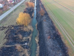 Irrigation canal with burned reeds along the shore. Ashes from the grass