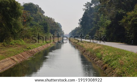 Irrigation canals and roads. Irrigation channels in concrete walls deliver water from reservoirs or dams to farmers' agricultural areas. On the background green trees and morning sky. Selective focus Stockfoto ©