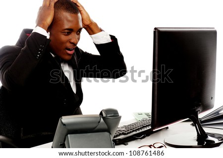 Irritated african man angry on computer at work stock photo