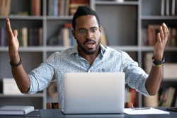 Irritated angry African American man wearing glasses having problem with broken laptop, confused unhappy businessman looking at screen, reading bad news in email, loss information or malware apps