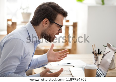 Irritated angry man sitting at the desk in office looking at laptop screen having problem, bad news. Side view of stressed, businessman noticed the error, failed to work, failure in business concept Photo stock ©